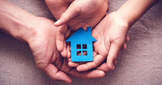 une maison bleu miniature est dans les pommes des mains d'un parent et son enfant